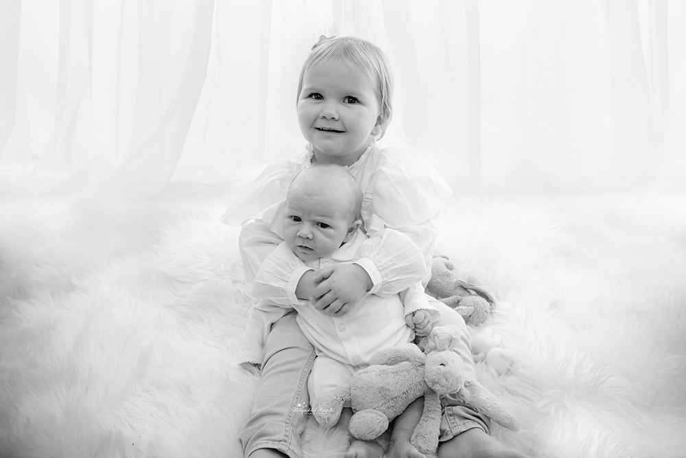 baby girl sitting on a white fluffy rug, holding her baby sister