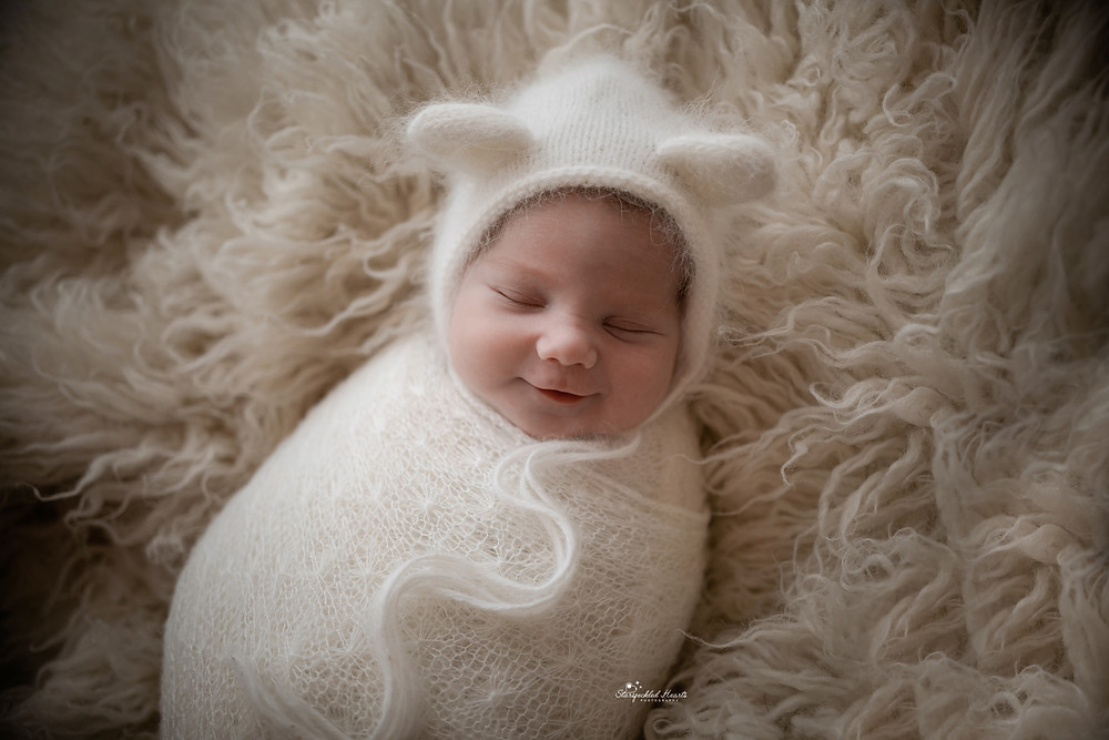 adorable sleeping newborn boy wearing a white knitted bear ear bonnet and swaddled in white