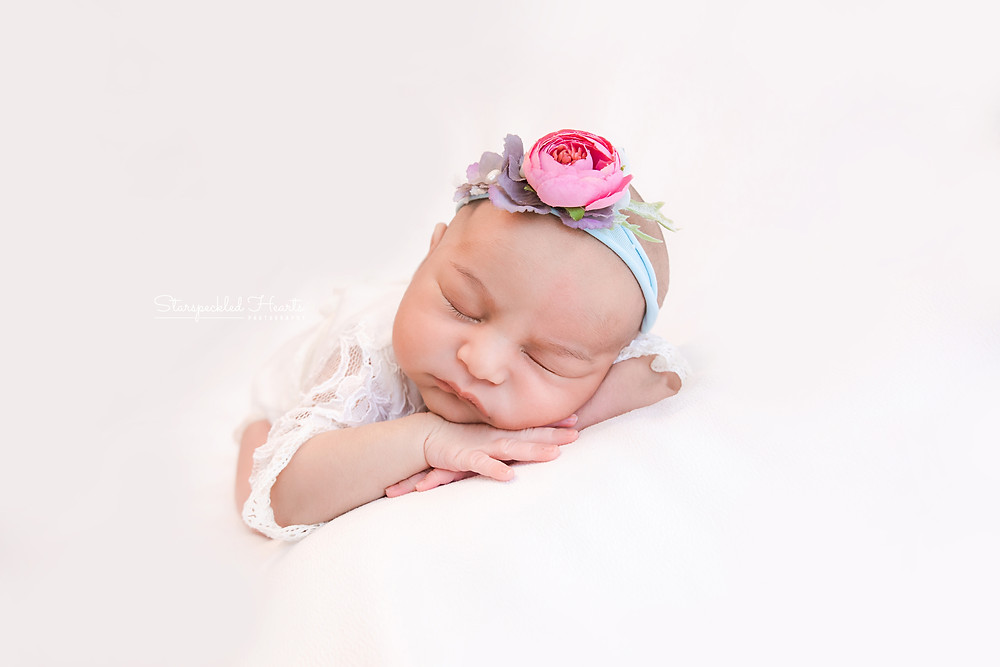 adorable newborn baby girl lying on her front on a white backdrop for her newborn photography session with starspeckled hearts photography in aldershot hampshire