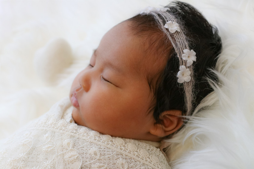 sleeping newborn girl wearing floral headband wrapped in white lace