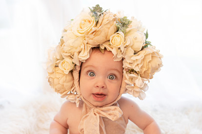 beautiful baby girl with big blue eyes and a large floral bonnet