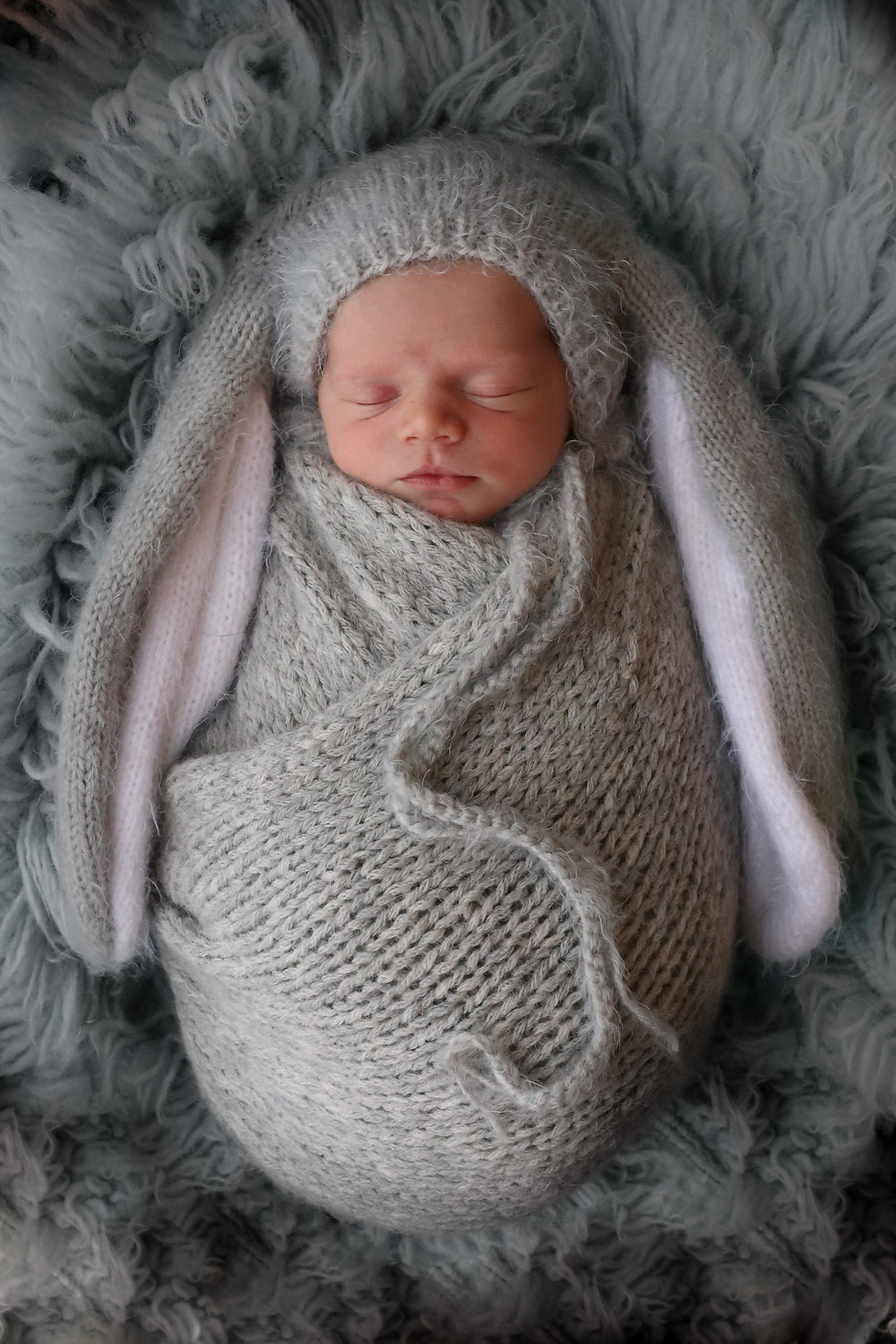 cute baby boy fast asleep, wearing a grey knitted bunny bonnet with long ears and matching grey knitted wrap