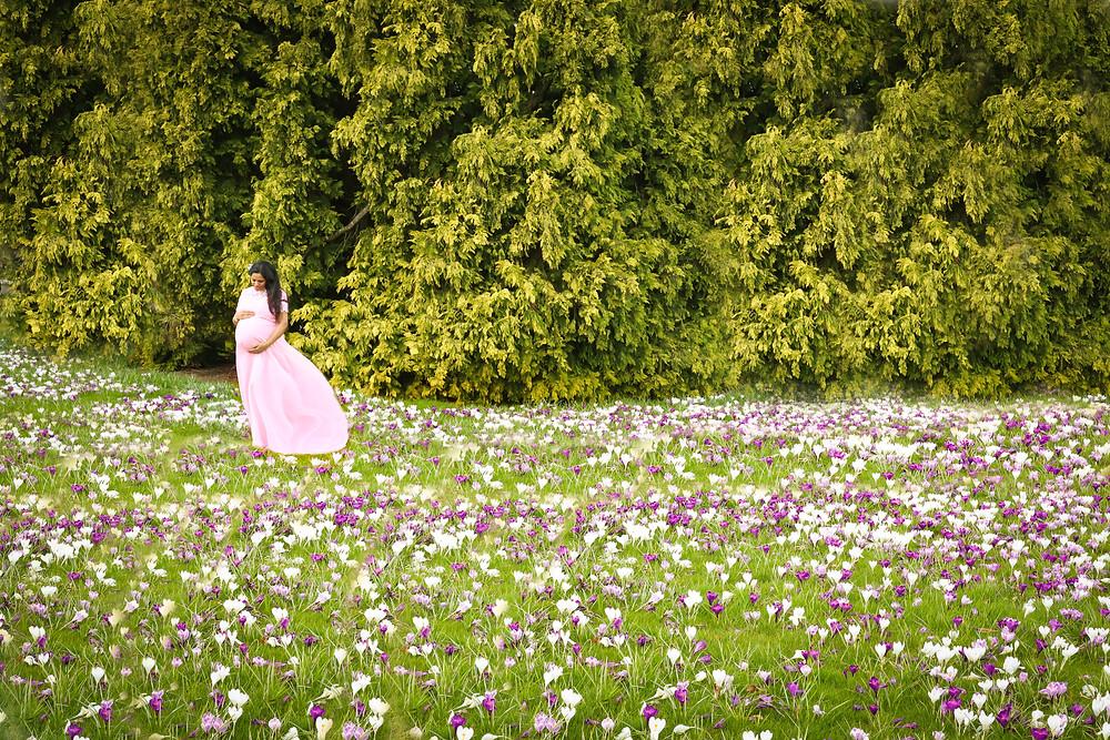 pregnant woman in pink dress in flower meadow