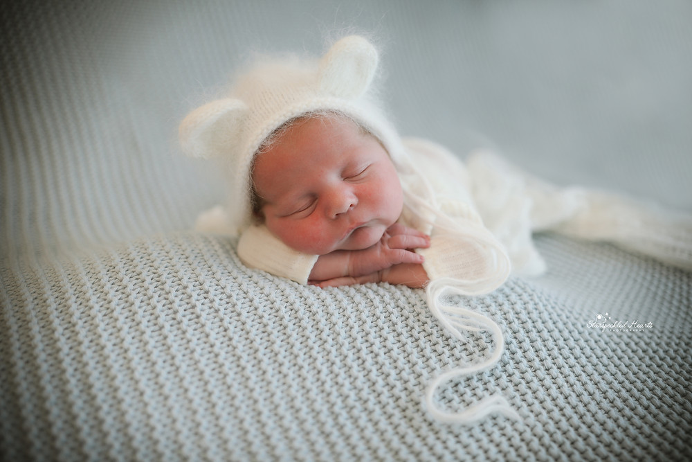 sleeping newborn wearing a knitted white hat with bear ears, head on hands