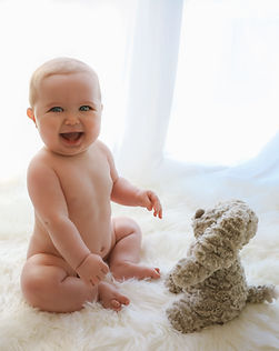 adorable smiling baby boy sitting up on a furry white rug with his puppy teddy