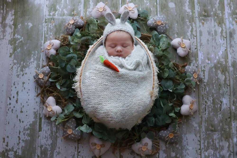 newborn boy wearing bunny bonnet lying in a basket