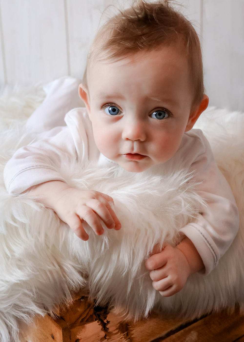 gorgeous baby with the biggest blue eyes and cute face, lying in a wooden crate stuffed with a white fluffy blanket