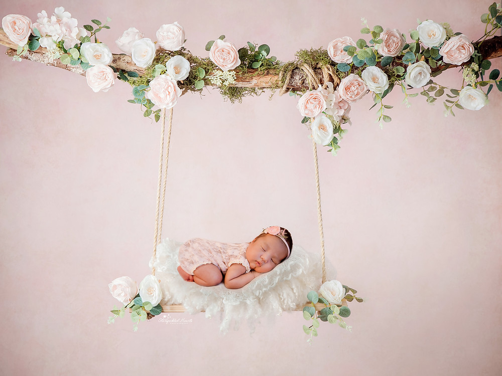 newborn baby girl on a floral swing for her newborn photography session