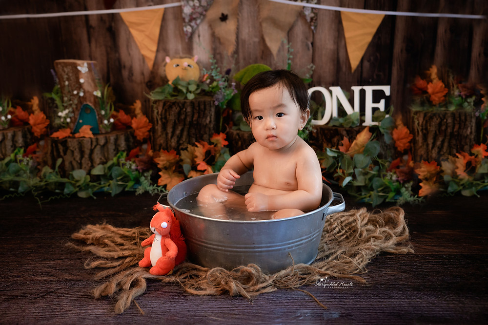 little boy in washtub with bubbles woodland themed cake smash