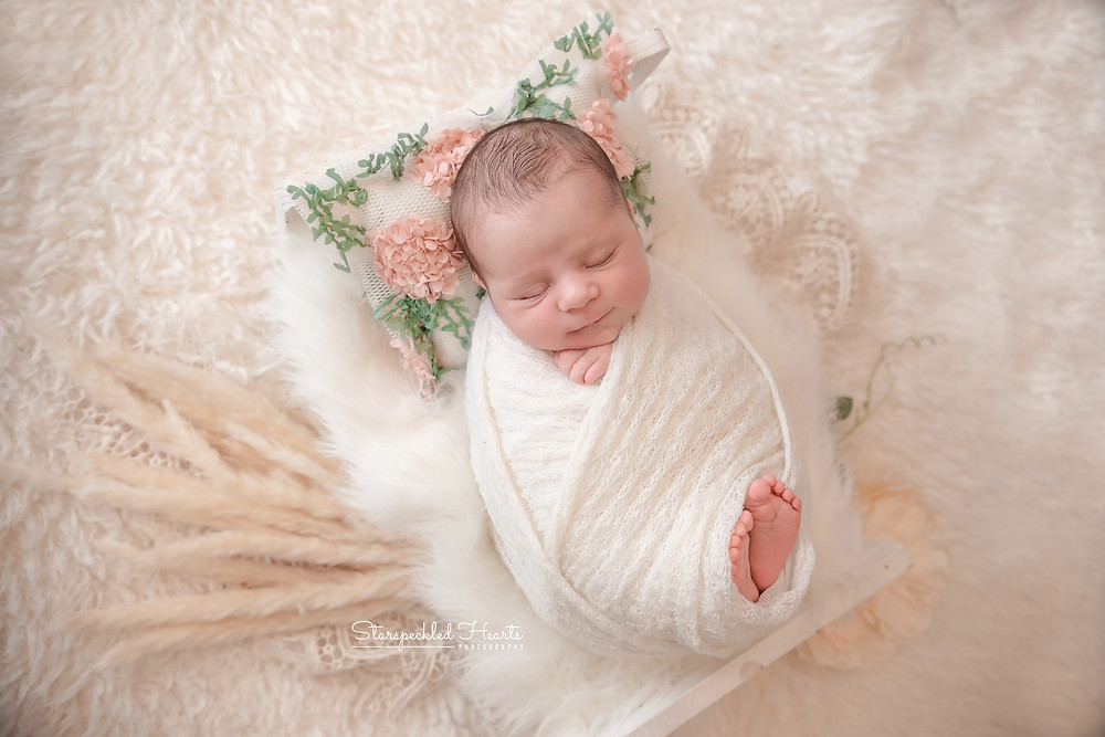 baby girl swaddled in white lying in a wooden bed on a white fluffy rug for her photography session with starspeckled hearts photography in caversham