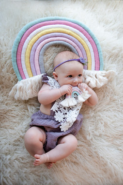 baby girl lying in front of a large macrame rainbow
