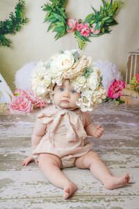 toddler girl sitting on floor wearing large flower bonnet