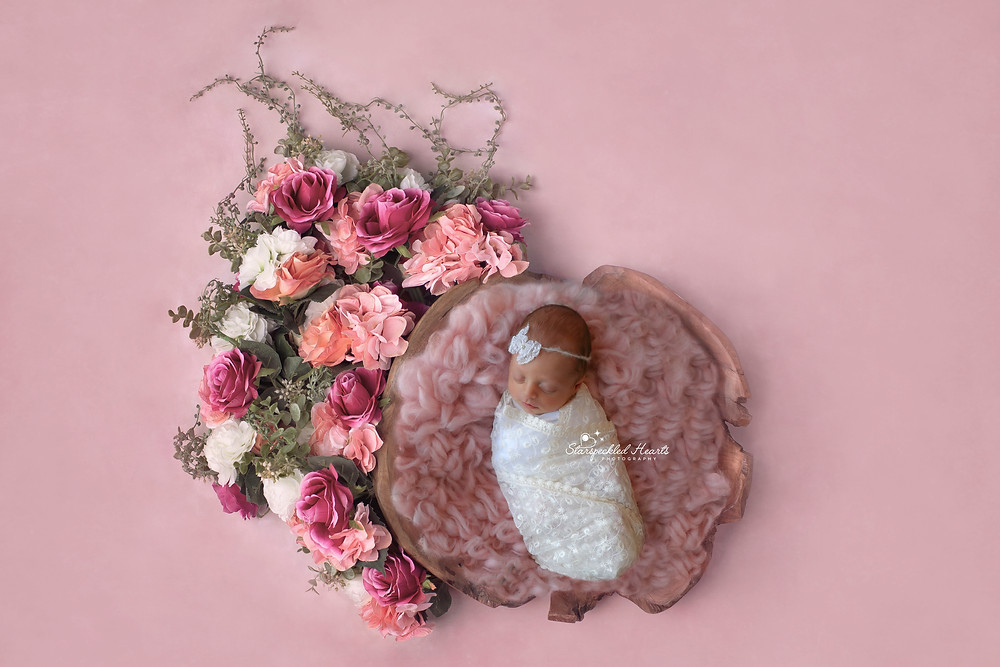 newborn girl in pink sleeping in a wooden bowl surrounded by large pink beautiful flowers on a pink background