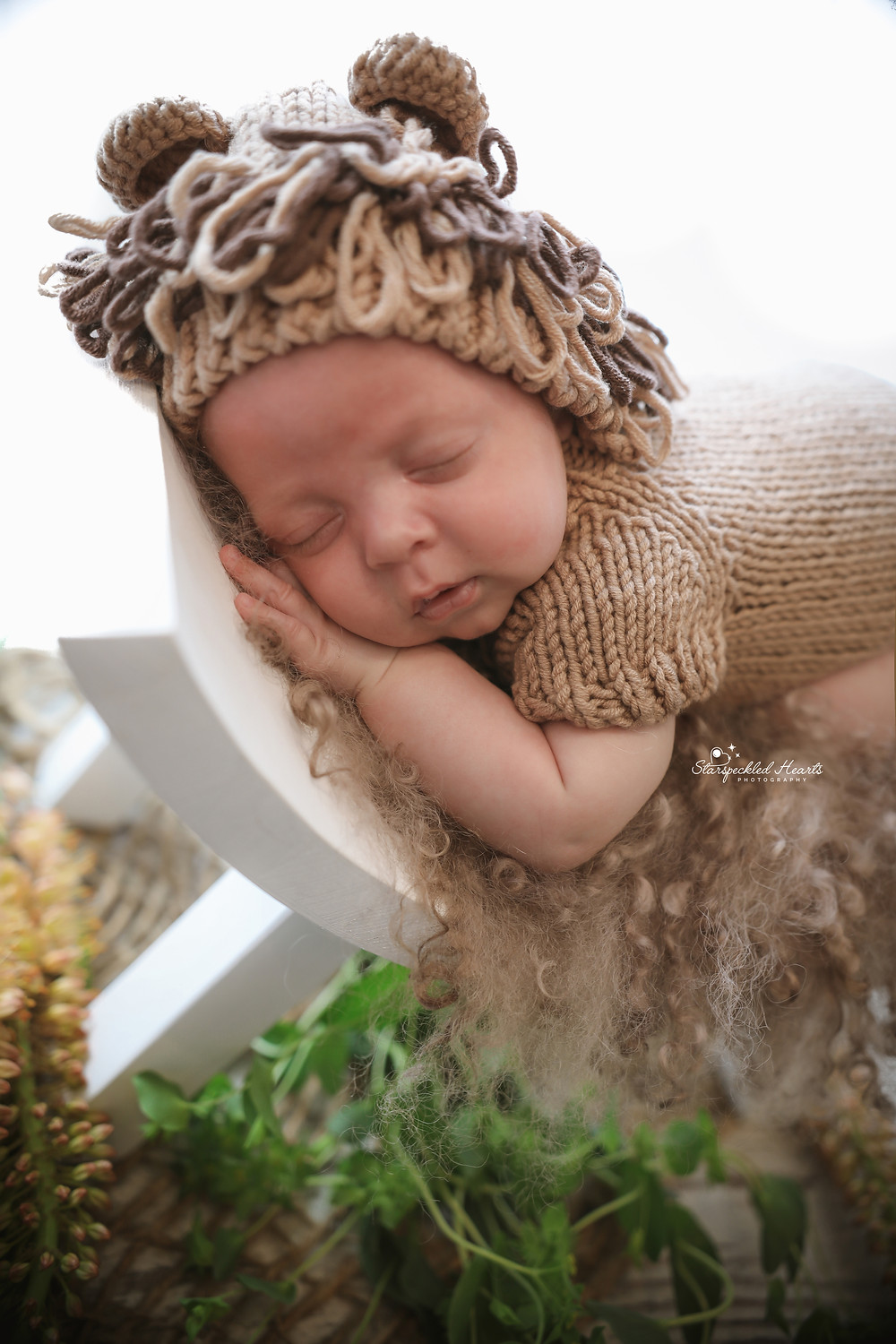 sleeping newborn wearing a brown knitted lion bonnet and matching romper, lying on a curve bench