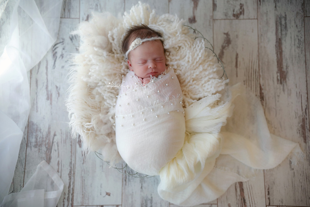 baby girl wrapped in a white pearl embellished wrap
