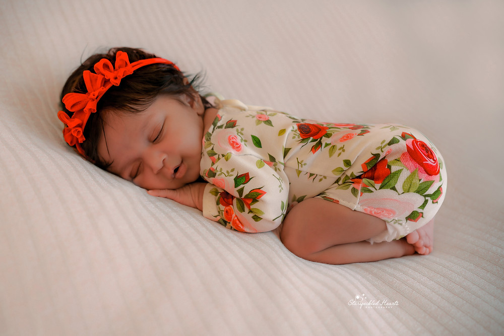 beautiful sleeping baby girl wearing a red headband, laying on a white textured blanket