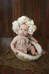 toddler girl sitting in wicker basket wearing large flower bonnet dark wood backdrop
