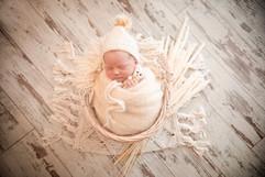 sleeping newborn in white cuddling a white teddy for his newborn session