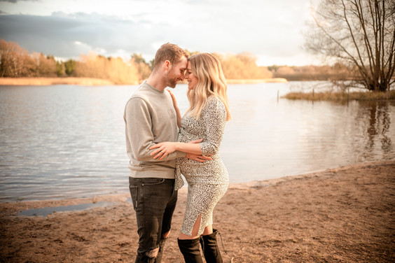 a pregnant woman and her husband in an embrace, standing near a large lake for their outdoor maternity session with starspeckled hearts photography in aldershot hampshire