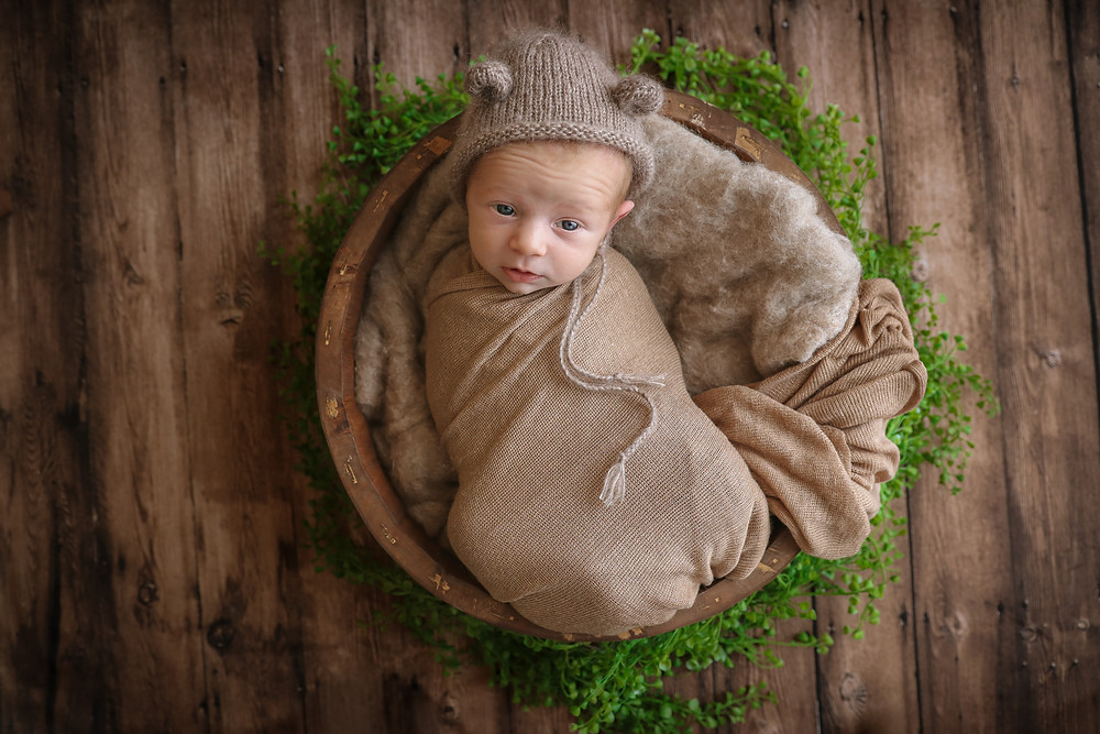 awake newborn lying in a bowl wrapped in brown fabric