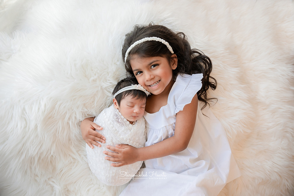 newborn baby girl lying on a white fluffy rug with her older sister, both wearing white for their newborn photography session in aldershot