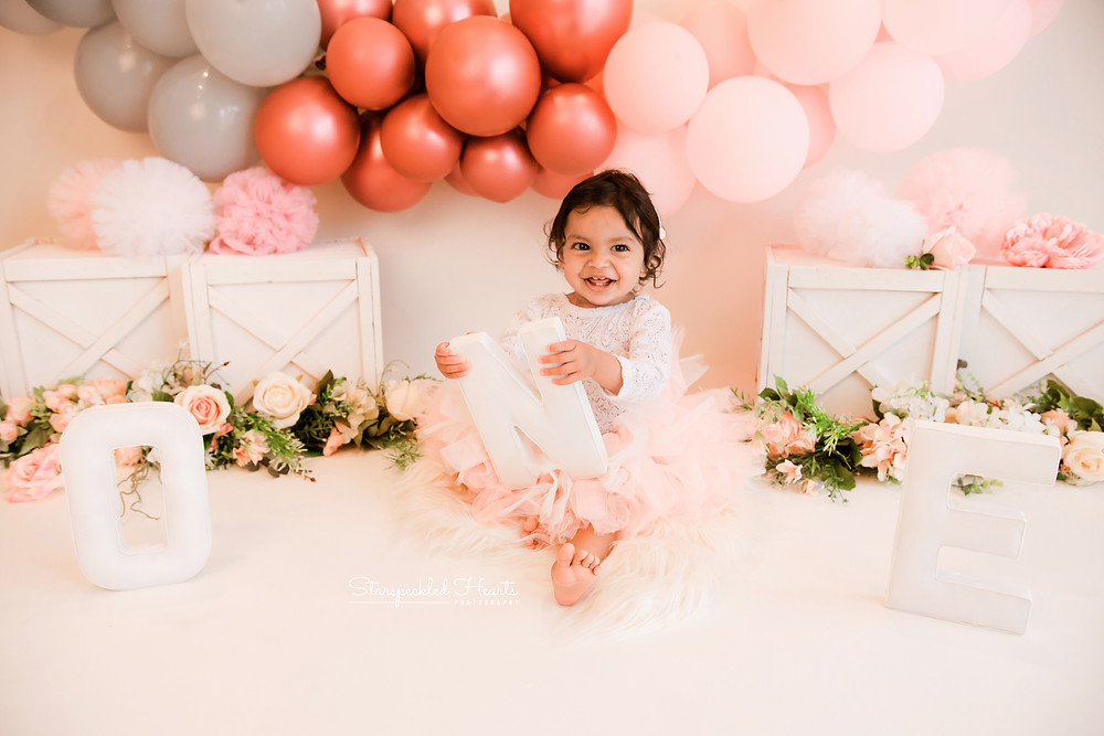A smiling baby girl sitting on the floor wearing a pretty pink tutu with a large balloon garland in the background for her first birthday cake smash and splash session in Aldershot, Hampshire