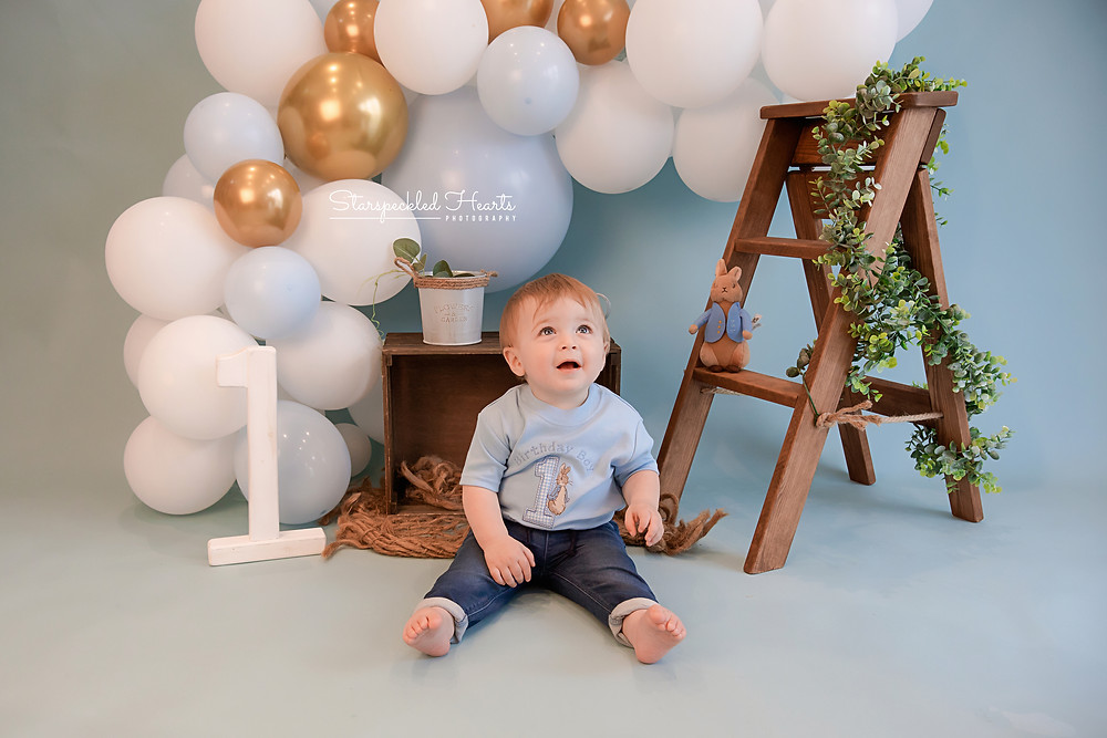 Peter Rabbit inspired 1st birthday cake smash session with blue gold and white balloons for adorable baby boy in aldershot hampshire