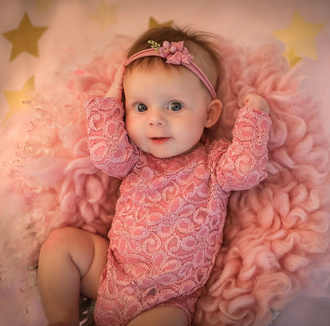 baby girl wearing a pink lace romper with matching headband lying on a pink fluffy rug for her little smiler session in hampshire