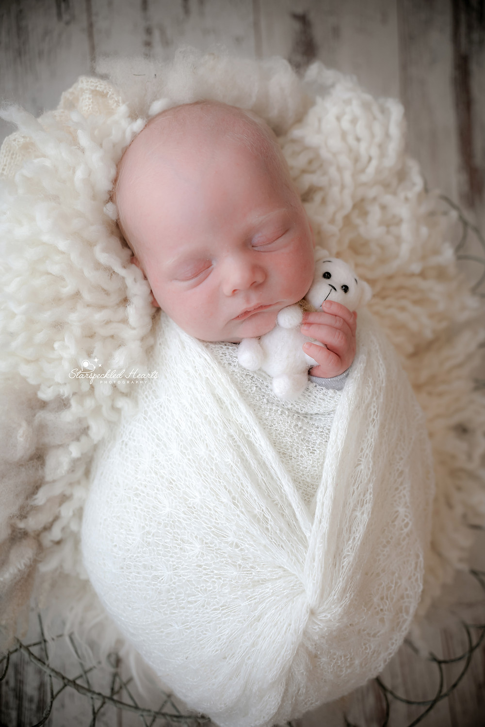 adorable sleeping newborn baby wrapped in white, cuddling a white teddy bear