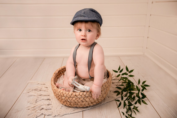 handsome baby boy wearing a flat cap and braces, sitting in a woven basket with greenery around it