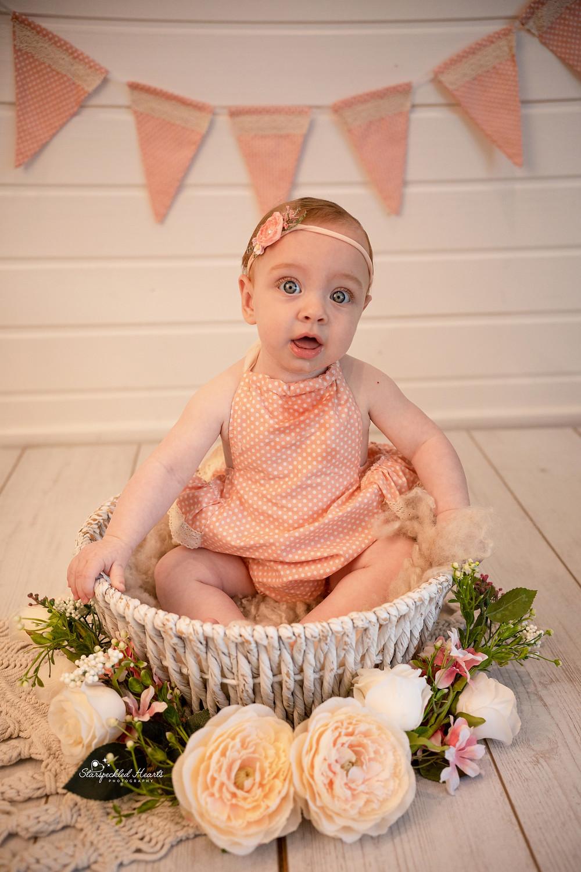 cute baby girl sitting in a basket wearing pink