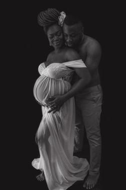 full body shot of pregnant woman wearing a white lacey sheer maternity gown and a bare chested man, embracing