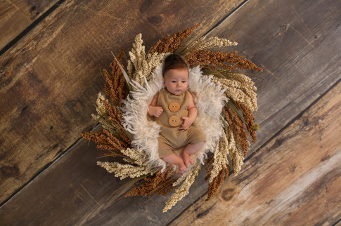 gorgeous baby boy laying in brown bowl wearing a brown romper with big buttons