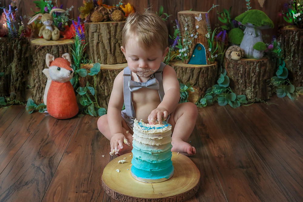 gorgeous baby boy wearing a grey bowtie and matching braces and shorts, grabbing a handful of blue cake, sitting in front of a woodland themed setup for a cake smash