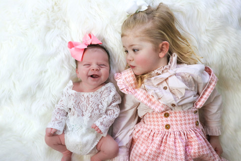 a blonde toddler girl wearing a pink checkered overall dress, laying next to her baby sister wearing a white lacy romper, laying on a white furry rug
