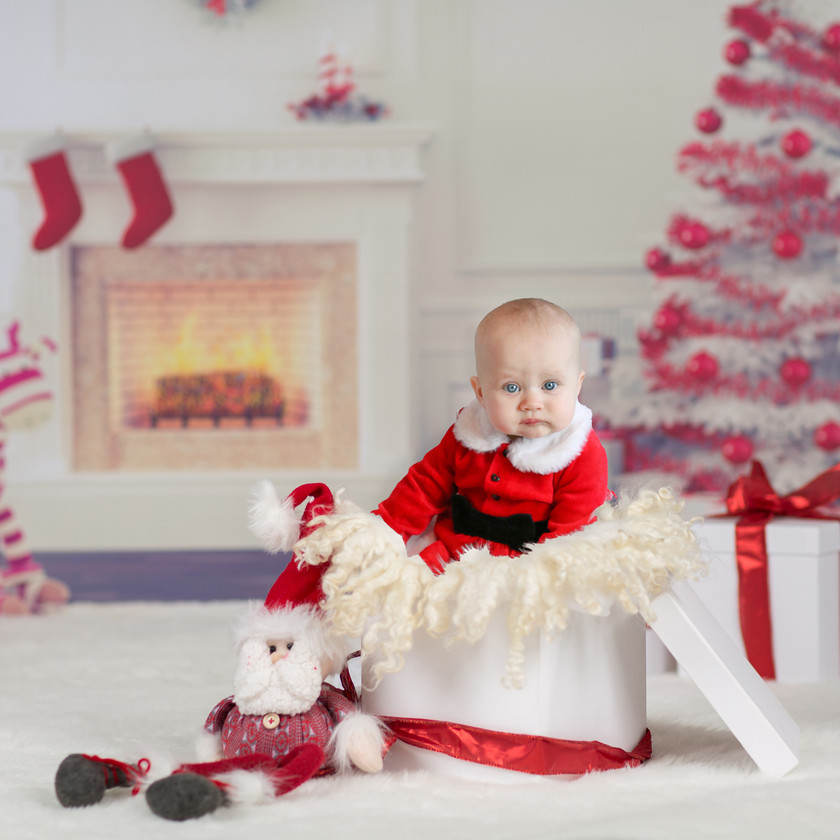 sweet baby girl wearing red santa claus christmas outfit with peter pan collar, sitting up in a white wooden crate stuffed with a white fluffy rug, with a fireplace and christmas tree in the background
