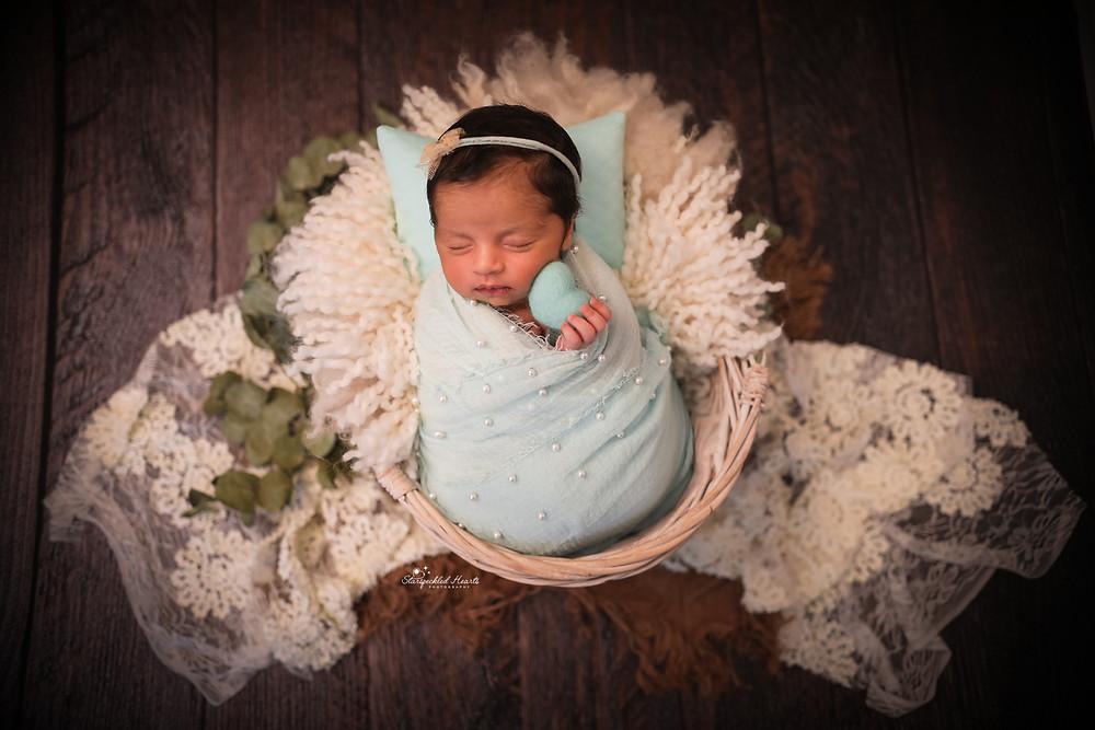 beautiful sleeping baby girl wearing a blue headband and a matching blue wrap