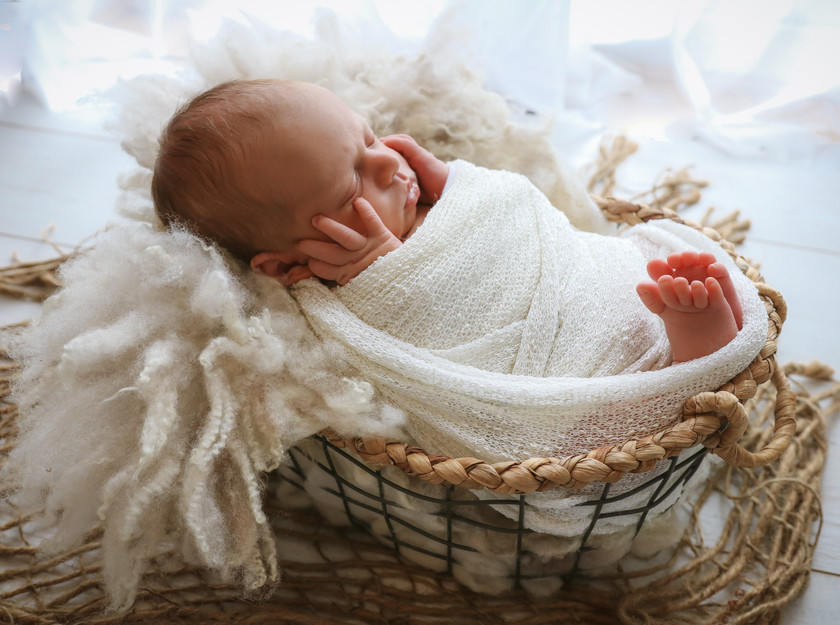 sweet newborn boy sleeping with hands on his face, lying in a wicker basket with a textured white wrap over him
