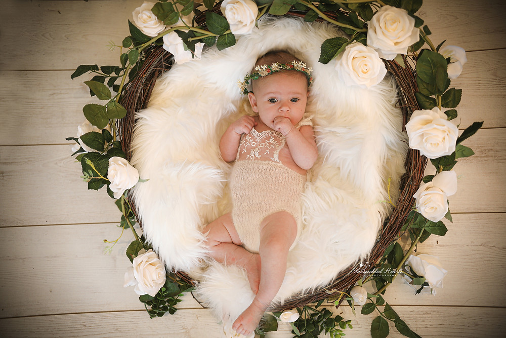 gorgeous baby girl wearing a lacey white romper, lying on a white fluffy rug in a round wicker basket