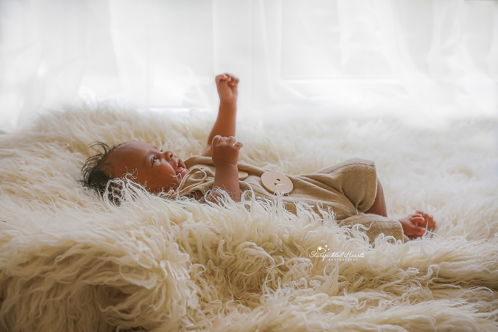 baby boy laying on a white fluffy rug, with his hands in the air, smiling