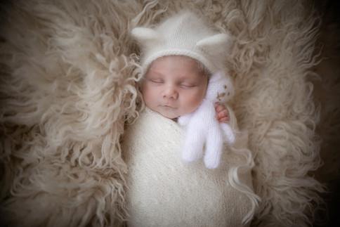 gorgeous sleepy baby boy in a furry white bear bonnet