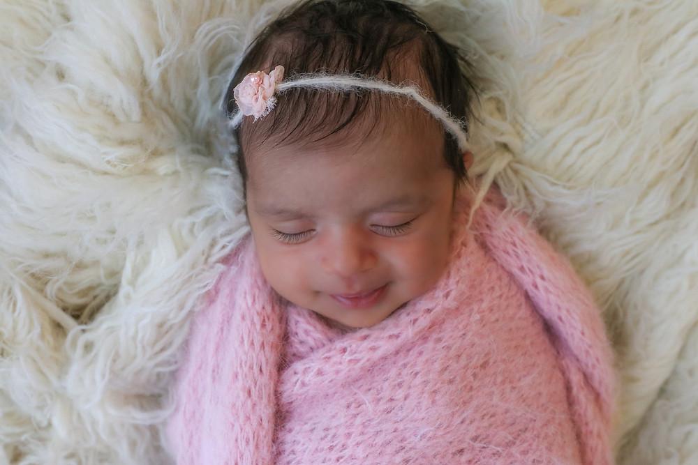 newborn girl in pink sleeping on white furry rug