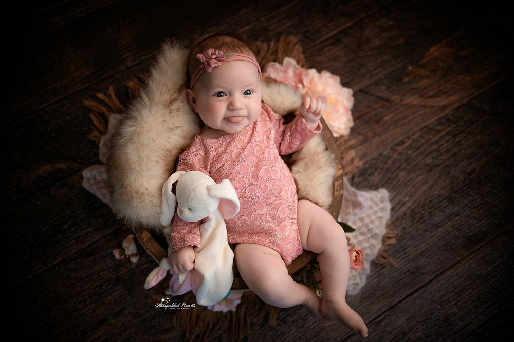 adorable baby girl wearing a pink lace romper sticking her tongue out whilst holding a bunny comforter, lying in a crate on a dark wooden backdrop for her newborn baby photography session in hampshire
