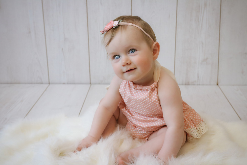 toddler girl sitting on white fluffy rug wearing pink romper suit