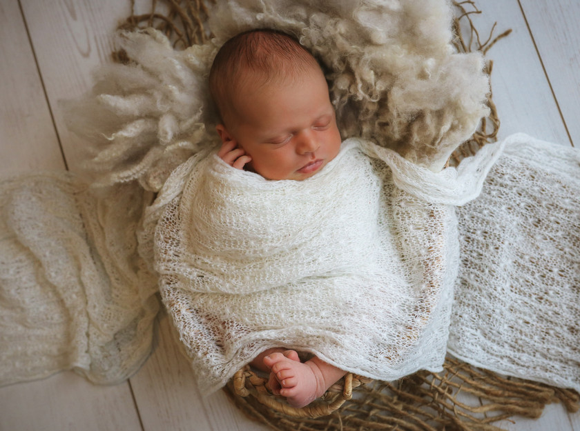 sweet newborn boy sleeping, lying in a wicker basket with a textured white wrap over him