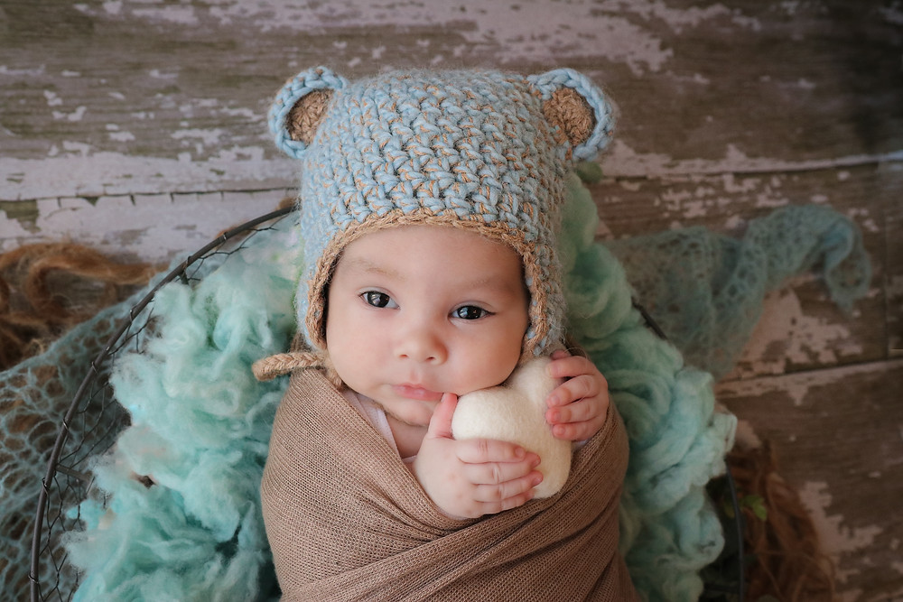 newborn baby boy with big eyes wearing a blue knitted hat with bear ears, clutching a felt heart in his hands