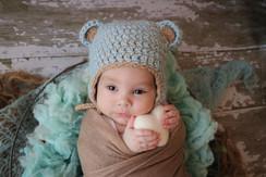 newborn in a blue and brown bonnet cuddling a white felt heart