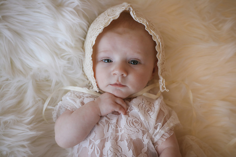 little girl wearing lace bonnet and vest