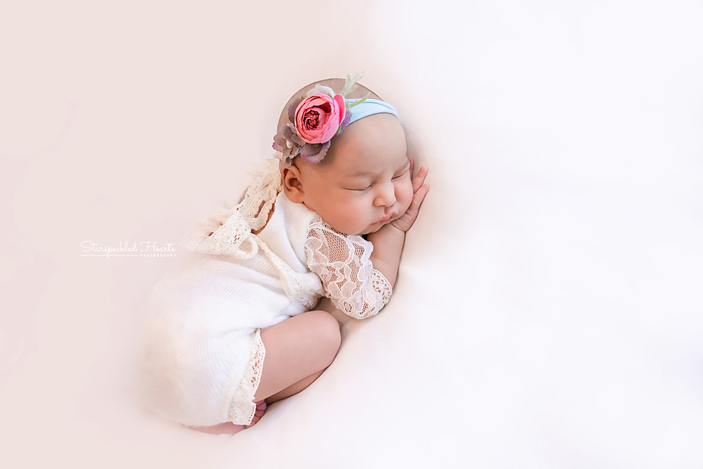 newborn girl wearing a lacy romper on a white backdrop for her newborn photography session in aldershot