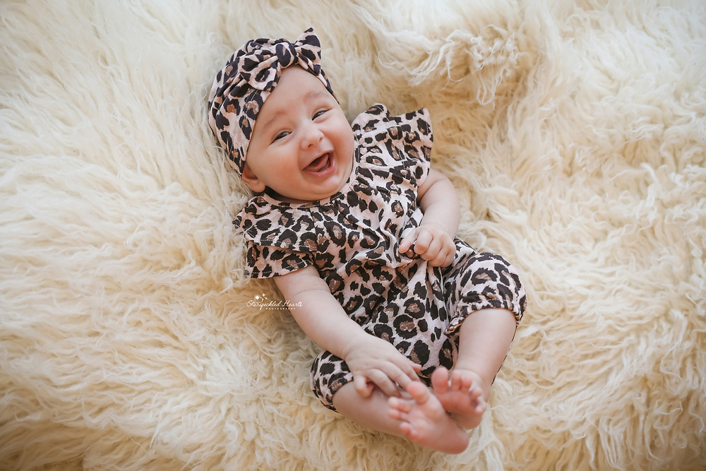 smiling baby girl lying on a white fluffy rug wearing a leopard romper